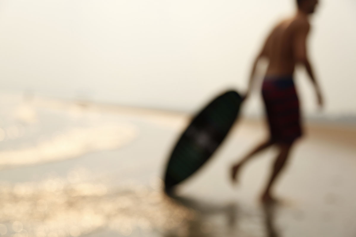 Skimboarder at the beach quirky defocused lifestyle photography by photographer Anthony Georgis | www.anthonygeorgis.com
